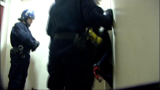 vídeos de stock, filmes e b-roll de london police smash people smuggling ring int various shots of police raiding flat folder entitled 'police evidence' arrested person seen in flat... - smuggling