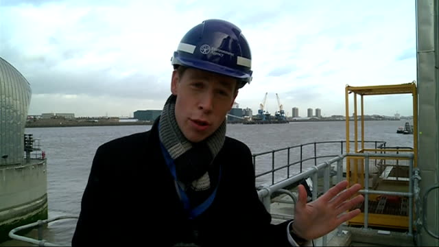 london prepares for storm reporter to camera cutaways industrial buildings on edge of thames small boat along in water with thames barrier in... - 2013 stock videos & royalty-free footage