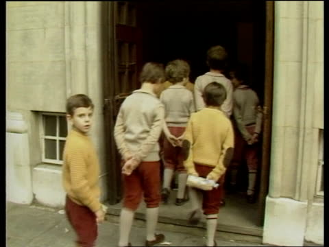 london pupils from hill house walk along pavement hill house bv pupils into school school pupils stand up in assembly r-l they sing the national... - pavement点の映像素材/bロール