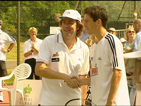 london: regents park: ext tennis player, tim henman, along holding cricket bat at charity tennis match henman and celebrity, jonathan ross, shaking... - jonathan ross english broadcaster点の映像素材/bロール