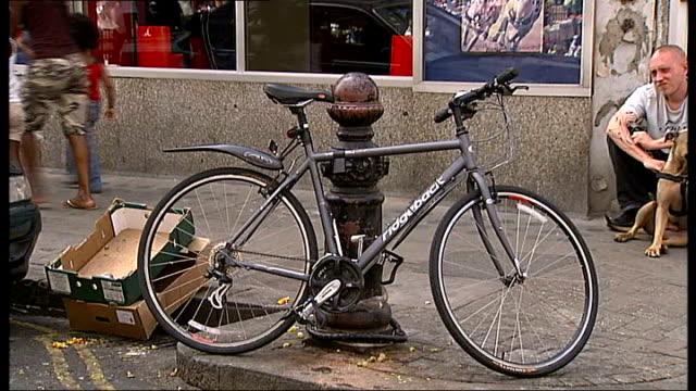 vídeos de stock e filmes b-roll de ridgeback mountain bike chained to bollard outside tesco metro supermarket graphicised shot as bike disappears from bollard - cadeia de lojas