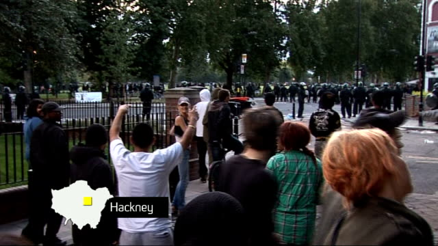 vidéos et rushes de further violence and unrest; london: hackney: riot police on street with fire burning outside house in background with 'hackney' graphic overlaid... - hackney