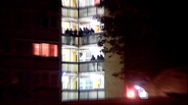 second night scenes of damage riot police and looting in Brixton Police restraining suspected looter / People watching from balcony on block of flats...