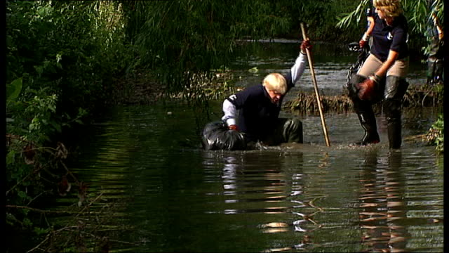 river pool: ext boris johnson wading thru river with volunteers who are clearing up stream johnson falling into river as volunteers rush to help him - river stock videos & royalty-free footage