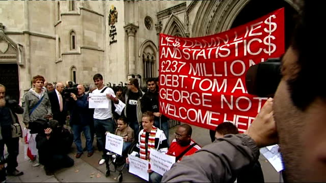 London Royal Courts of Justice EXT Liverpool football fans chanting and with protest banner outside High Court SOT Liverpool FC fan holding up notice...