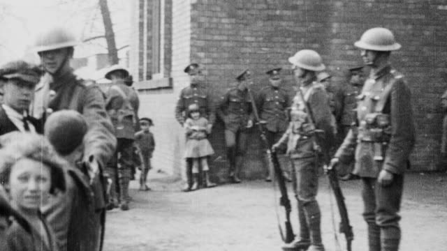 1921 WS London Scottish reservists maintaining a presence on the streets, with one soldier gently pushing back a crowd of children / London, England