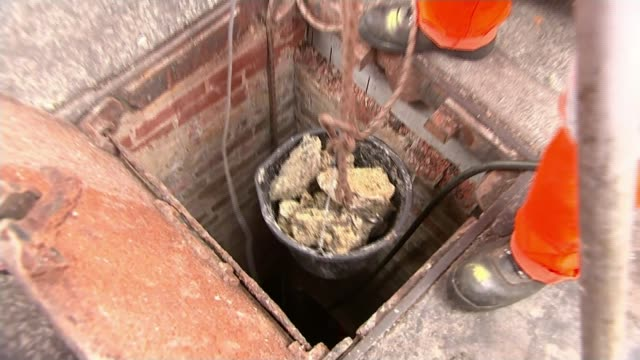 London sewers clogged up with wet wipes T12091717 / 1292017 EXT Bucket containing part of 'Fatberg' lifted from sewer by workers Workers wearing...