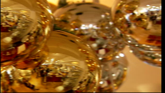 London shops open Christmas departments in August Close up gold and silver baubles PAN