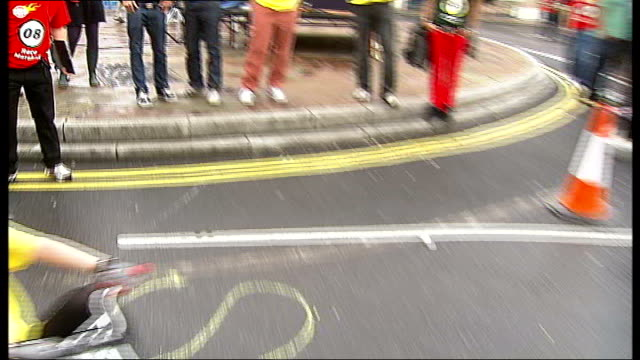 London Shoreditch EXT Man in cycling gear putting on yellow shorts Man writing in chalk in Bicycles Only parking zone Women wearing headphones in...