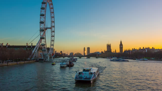 London skyline with London Eye and Houses of Parliament and boat on River Thames seen at sunset from Hungerford Footbridge.