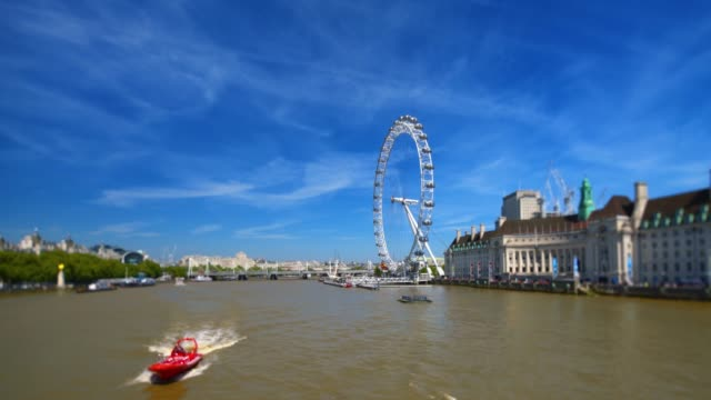 london skyline with london eye observation wheel and a speed boat on river thames. - building exterior stock videos & royalty-free footage