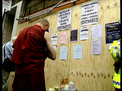 london: soho: ext flowers laid outside boarded up front of admiral duncan pub which was damaged in nail bomb attack tilt up people gathered for vigil... - in front of点の映像素材/bロール