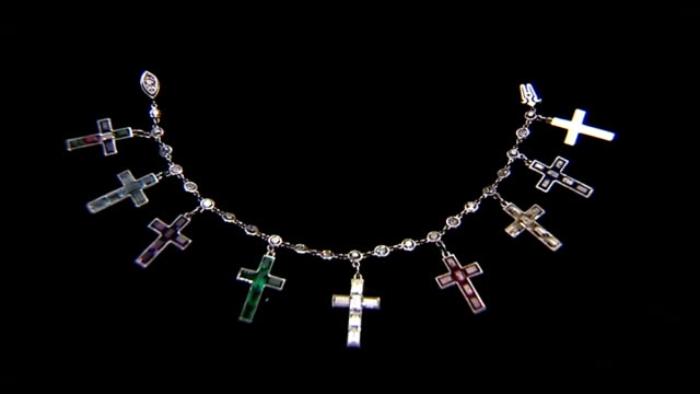 London Sotheby's INT Close shots of Wallis Simpson diamond charm bracelet with religious crosses Reporter to camera displaying diamond panther...