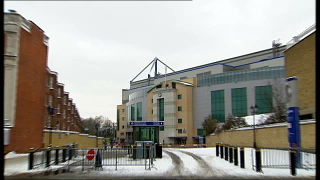 stamford bridge: ext / snow 'chelsea football club' sign on wall pull out to general view of stamford bridge two people along on icy pavement outside... - peter snow stock videos & royalty-free footage