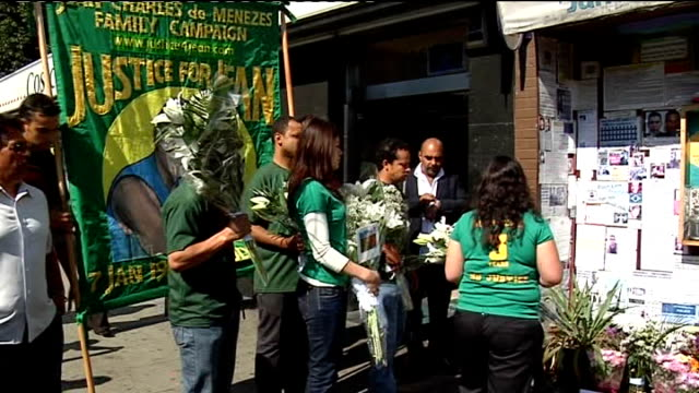 london stockwell ext friends and family of jean charles de menezes along to station with flowers on third anniversary of his shooting banner above... - ストックウェル点の映像素材/bロール