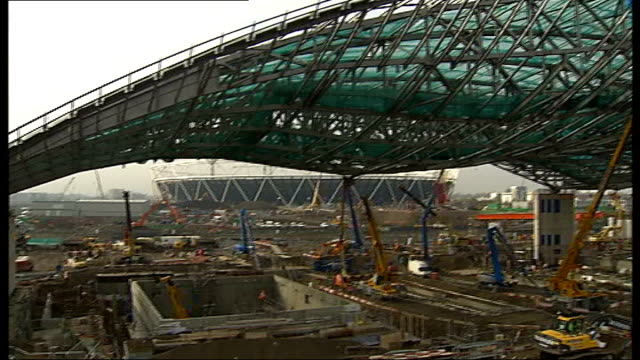 london stratford olympic site ext close shot of steel girders of aquatic centre roof pull out to gv workmen under roof in cherry picker pan frame of... - waving icon stock videos & royalty-free footage
