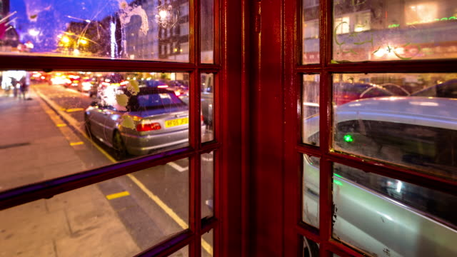 london street life timelapse from inside phone booth - 電話ボックス点の映像素材/bロール