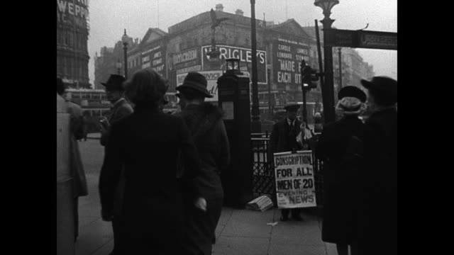 london street pedestrians english men handing out newspapers. vs sign '...all men of 20 300 000 conscripts.' men walking w/ rifles. ext vs men... - 1939 stock videos & royalty-free footage