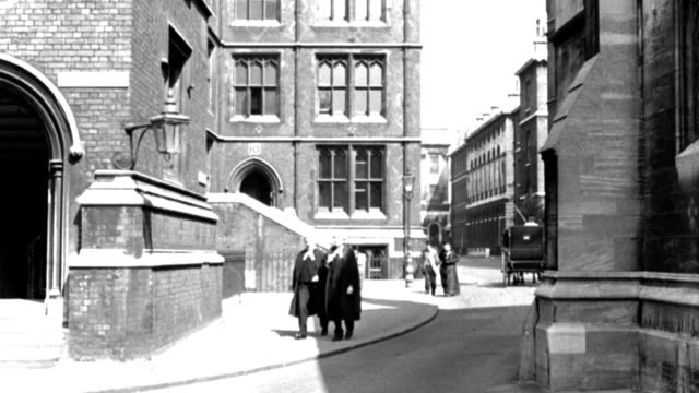 "dx - london streets - 1890's - no automobiles - new law courts - down a street - buildings sides - sign on building l: ""old square"" - two robed barristers forward and out camera l as a two-horse closed carriage enters f.g. - to b.g. - b&w. - horse family stock videos & royalty-free footage"