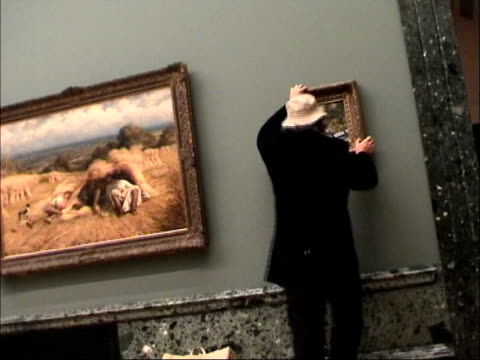 london tate britain int bv banksy disguised as an old man hanging his ersatz old master painting 'crimewatch uk has ruined the countryside for all of... - バンクシー点の映像素材/bロール