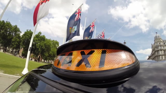 stockvideo's en b-roll-footage met london taxi driving through westminster - alle vlaggen van europa