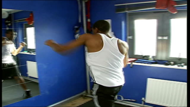 london teenagers encouraged to take up sport instead of gun crime; england: london: deptford: int anthony small practising boxing punches in front of... - fade out video transition stock videos & royalty-free footage