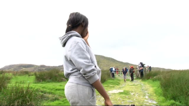 london teenagers return from snowdonia trip t13081016 snowdonia ext girl dragging backpack along mountain path - snowdonia video stock e b–roll