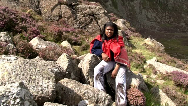 london teenagers return from snowdonia trip t13081016 snowdonia ext tope samuel sitting on rock as saying 'this is not shopping on oxford street' sot - snowdonia video stock e b–roll