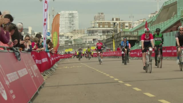 sussex brighton ext various shots cyclists along road in brighton at finish of london to brighton bike ride 2016 vox pops [cyclists] - itv london tonight weekend点の映像素材/bロール