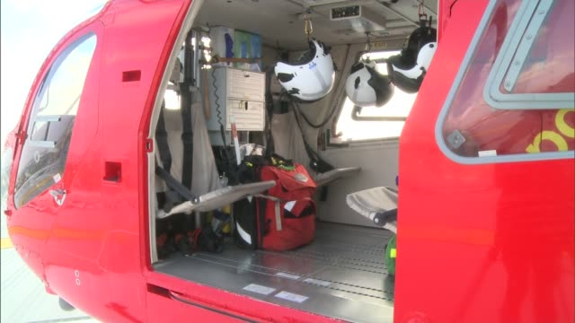 london to get second air ambulance england london ext air ambulance on helipad inside of air ambulance seen through open door close shot helmet... - helicopter landing pads stock videos and b-roll footage