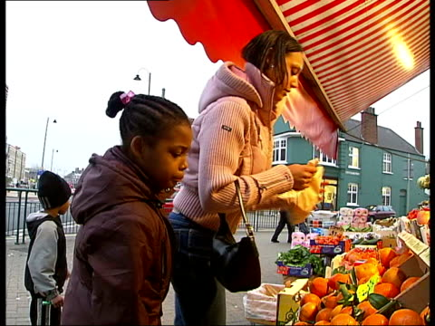 tooting: ext jacquie bullen towards with two children int powell pushing shopping trolley along into supermarket i/c as weighing satsumas ext bullen... - tag 1 stock-videos und b-roll-filmmaterial