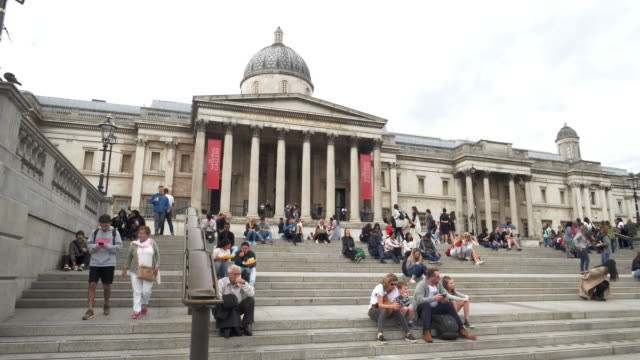 london tourists resting in front of the national gallery - トラファルガー広場点の映像素材/bロール