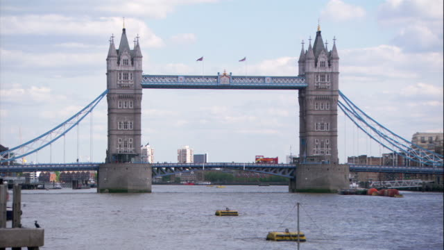 london traffic moves across the tower bridge spanning the thames river. - fluss themse stock-videos und b-roll-filmmaterial