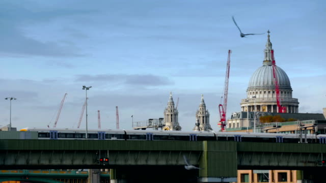 london. train moving on bridge and st paul's cathedral at distance - restoring stock videos and b-roll footage