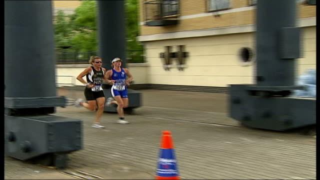 vídeos de stock e filmes b-roll de london triathlon; two female triathletes running along and picking up drinks from refreshments table - triatleta