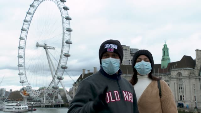 members of the public pose with face masks on in front of the london eye at coronavirus in london on march 11 2020 in london england - human face stock videos & royalty-free footage