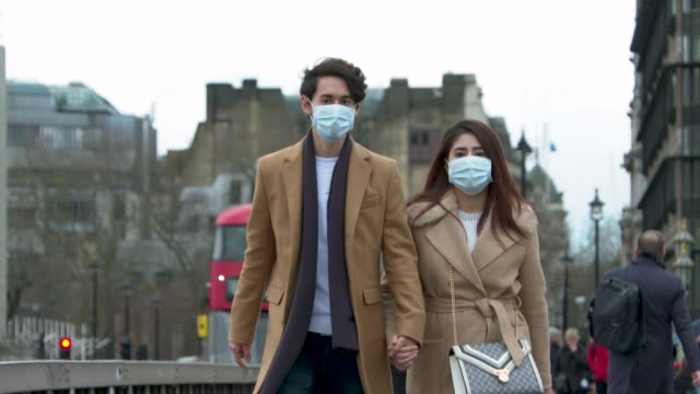 couple walk with face masks on over westminster bridge at coronavirus in london on march 11, 2020 in london, england. - couple relationship stock videos & royalty-free footage