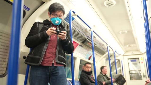 slomo a member of the public wears a protective face mask on the london underground due to the world wide outbreak of covid19 at coronavirus in... - wide stock videos & royalty-free footage