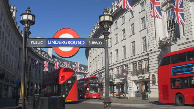 london underground early morning with union jacks and red buses - bandiera del regno unito video stock e b–roll