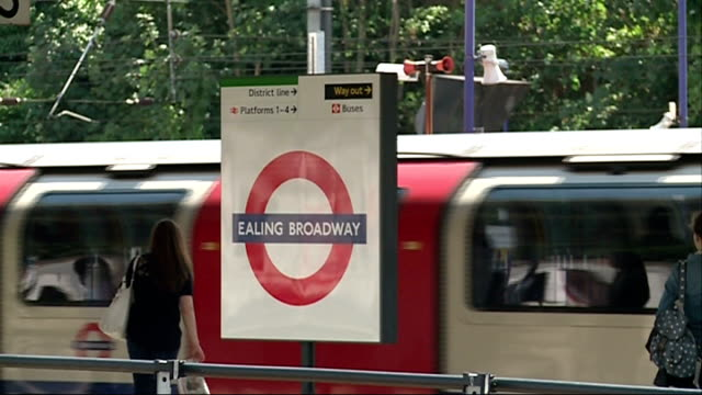 """""""end of the line"""" series: ealing; england: west london: ealing: ext gvs 'ealing broadway' sign on platform of tube station as trains pull in close... - rolling stones stock videos & royalty-free footage"""