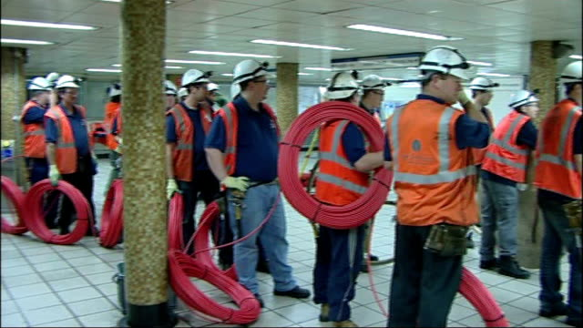 vídeos de stock, filmes e b-roll de london underground maintenance engineers away into green park station int maintenance workers holding cables and equipment down escalator engineer... - parque green