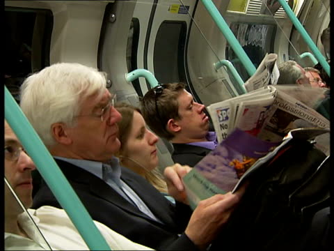london underground passengers boarding train / sitting in carriage; int train passengers sitting reading newspapers in fairly busy tube carriage... - daily mail stock videos & royalty-free footage