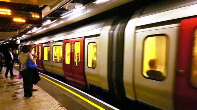 london underground train arriving at the station - schienenverkehr stock-videos und b-roll-filmmaterial