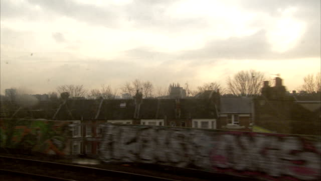 A London Underground train passes residential neighborhoods in London. Available in HD.