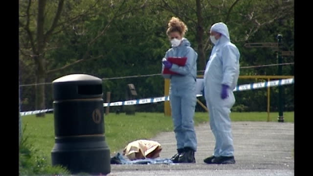 waltham forest: seymour road playing fields: ext police forensic officers search path in park - where body of 27-year old male shooting victim found... - investigatore video stock e b–roll