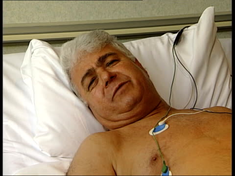 london wellington hospital int angina patient hasan mustafa lying on bed as hooked up to external counter pulsation treatment machine which uses... - after life stock videos & royalty-free footage