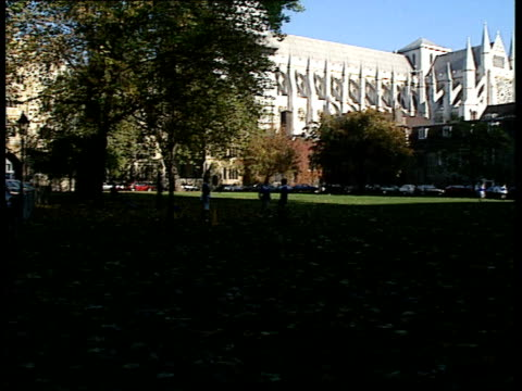 london: westminster: church green: church house: gvs westminster abbey from green, boys playing football in f/g/ churchman along street. gvs church... - synod stock videos & royalty-free footage