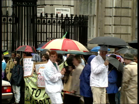 THATCHER ENGLAND London Whitehall Anti Apartheid demonstrators at Downing Street gates in Whitehall / ANC flags flying / demonstrators with umbrellas...