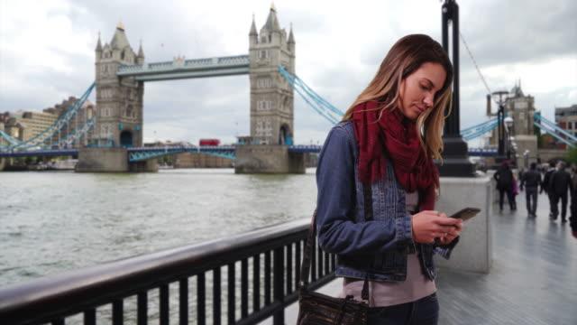 vidéos et rushes de london woman texting with mobile phone outdoors - london bridge angleterre