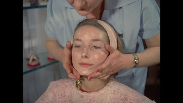 1961 - london - young women have foundation makeup applied - beauty salon stock videos and b-roll footage